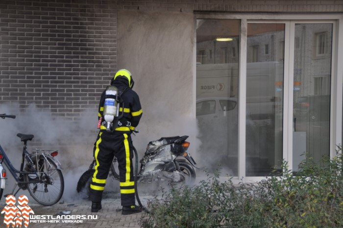 Scooter in brand tegen gevel appartementencomplex