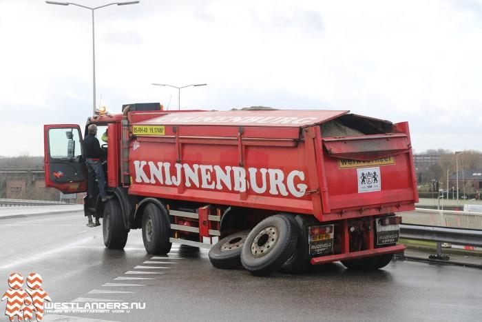 Volgeladen zandwagen verliest wielen