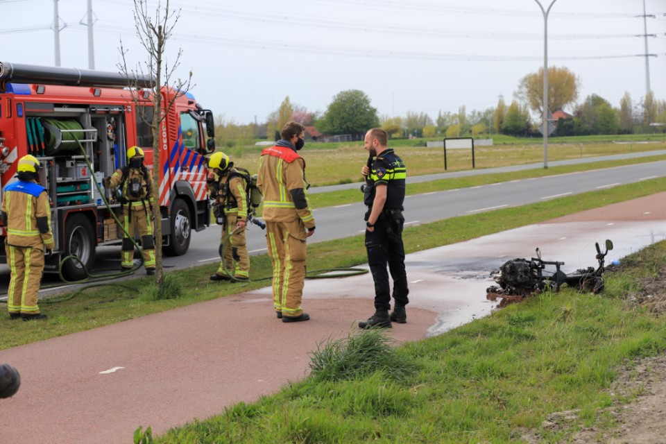 Snorscooter langs de weg uitgebrand